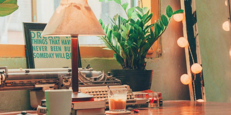 Bureau voor het raam met oude typmachine, lamp, plant, stapel boeken en koffiekopjes - uitgelichte afbeelding bij Writing for Fun and Sanity workshop review