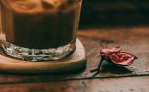 Close-up van glas koffie en droogbloemetje - decoratieve afbeelding bij Writing for Fun and Sanity